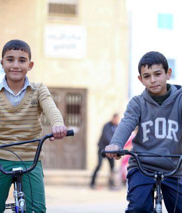refugee boys enjoying their charicycle bikes
