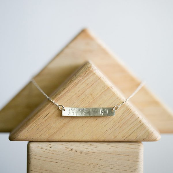 sterling silver branded collective ethical bar necklace on display case