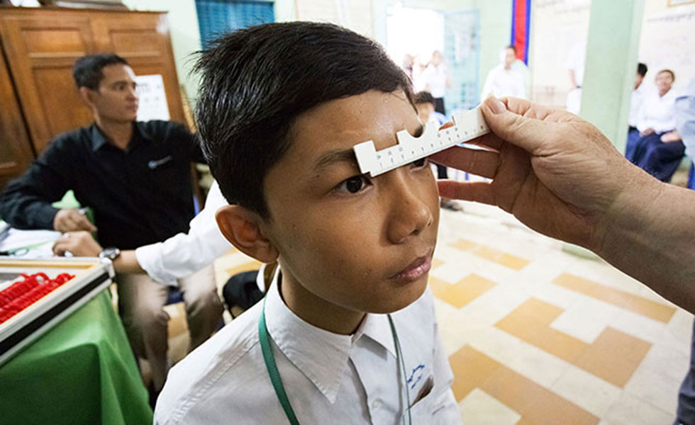 Cambodian boy getting eye exam from optometry giving sight